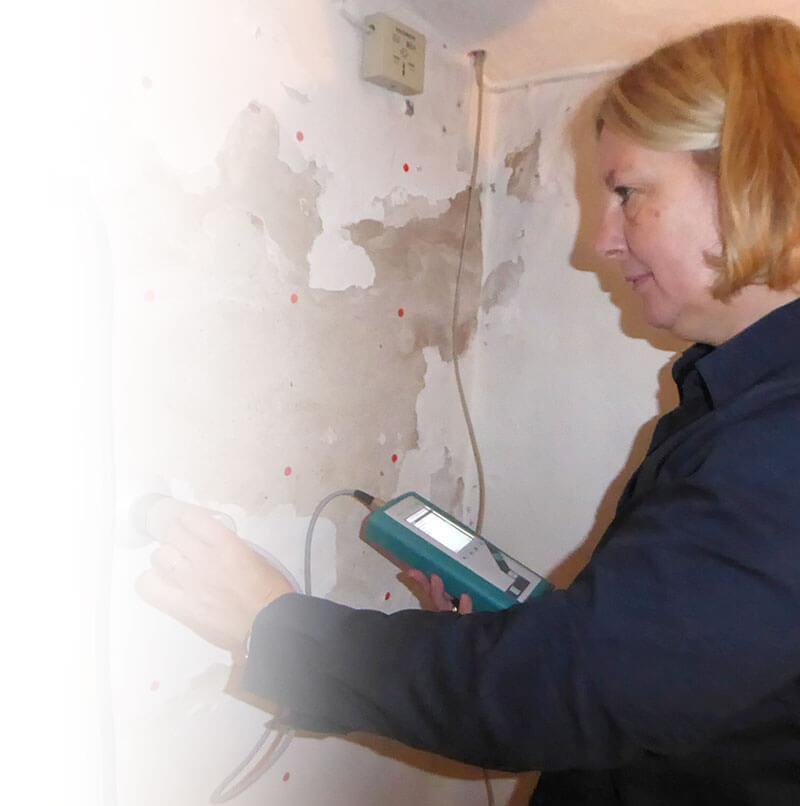 Prüfung der Wand auf Feuchtigkeit.